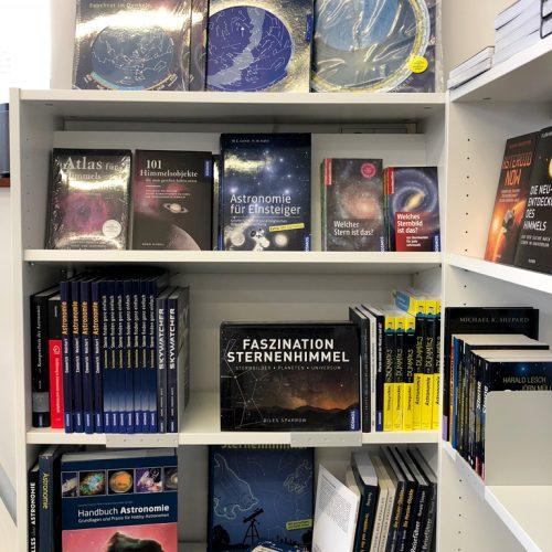 Buchregal mit Bücher über Astronomie und Sternkarten
